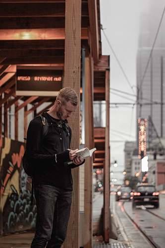 people man in black sweater stands on sidewalk with book in hand human