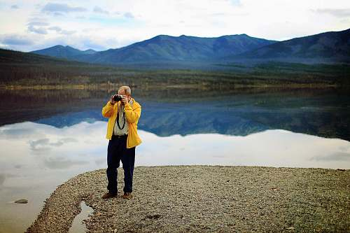 human man in yellow jacket taking pictures during daytime people