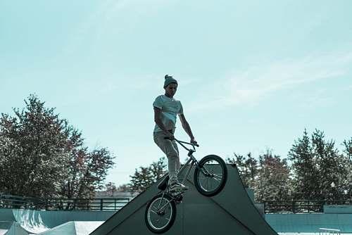 human man riding BMX bicycle during day time people