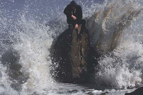 sea man seating on stone in between waving sea ocean