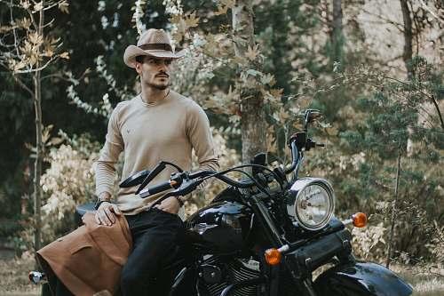 human man sitting on black motorcycle besides trees at daytime people