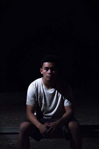 human man sitting on ground with black background people