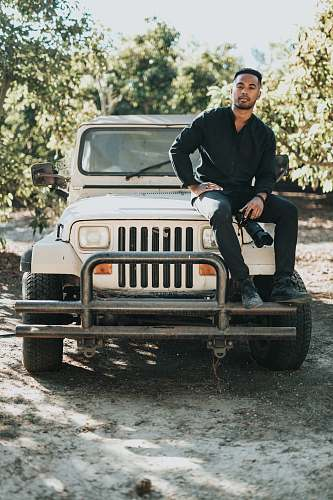human man sitting on white Jeep Wrangler SUV near trees during daytime people
