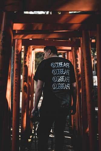 people man standing in between orange metal frames human