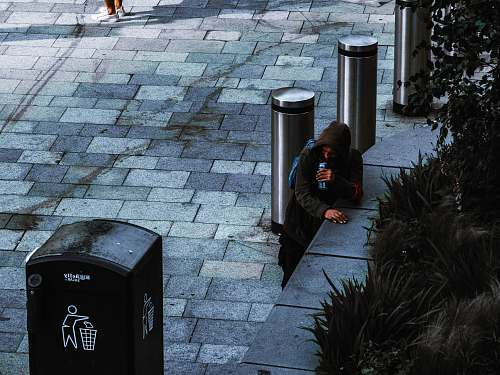 people man standing near black trash bin human
