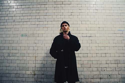 human man standing near gray brick wall people