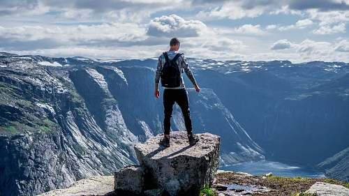 human man standing on edge of cliff mountain