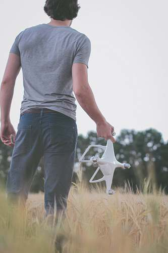 human man standing on field holding white quadcopter people