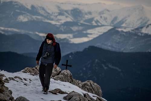 human man standing on peak near cross at daytime people