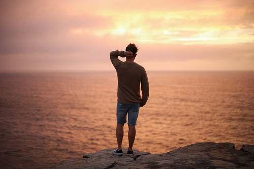 human man standing on rock near seashore during sunset people