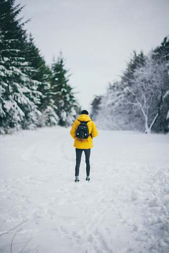 human man standing on snowfield while carrying backpack during daytime people