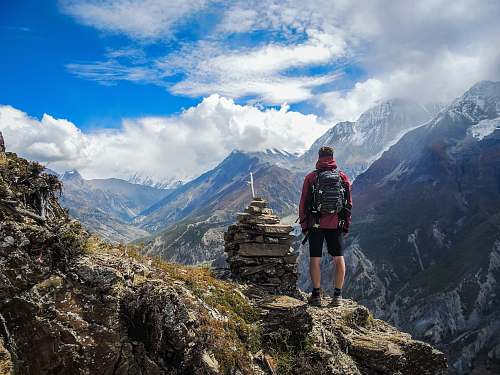 mountain man standing on top of mountain beside cairn stones mountain range
