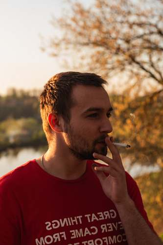 people man standing smoking cigarette near body of water and trees human