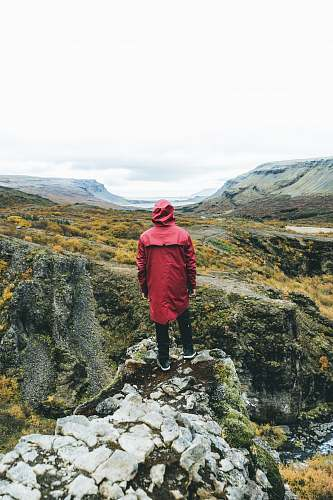 people man standing wearing red jacket on top of mountain human