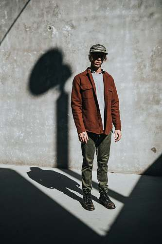 human man stands near concrete wall with shadow people