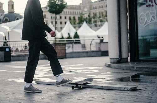 human man stepping on skateboard people