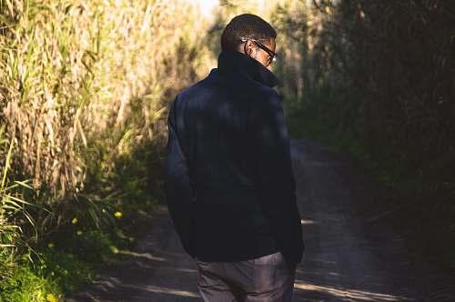 human man walking near green leafed plants people