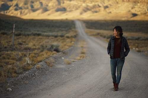 people man walking on gray soil road road