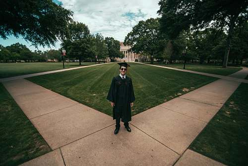people man wearing academic gown standing on green field human