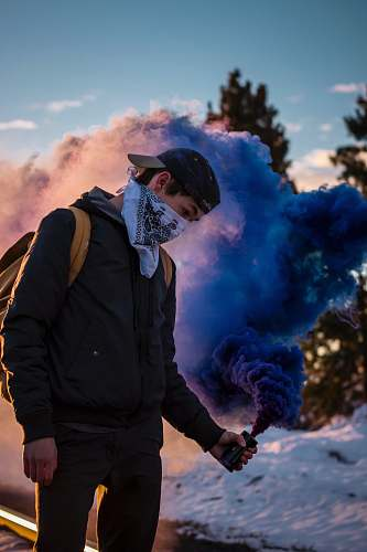 people man wearing bandana holding blue smoke can standing human