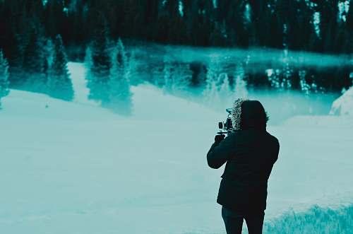 human man wearing black hoodie jacket while standing on snow covered pathway people