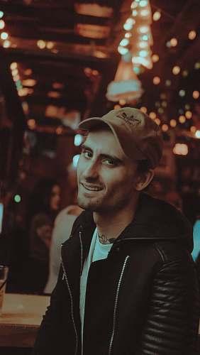 people man wearing black jacket smiling inside brown room human