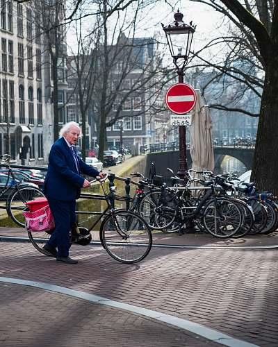 bicycle man wearing black notched lapel suit jacket holding bike bike