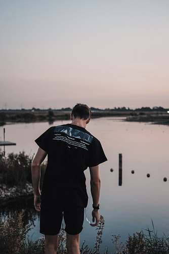 human man wearing black shirt near lake people