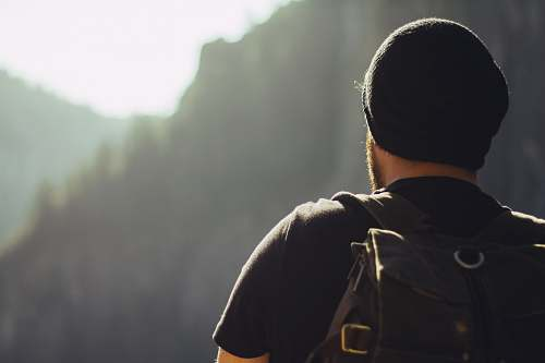 people man wearing black t-shirt and knit cap fronting mountains man