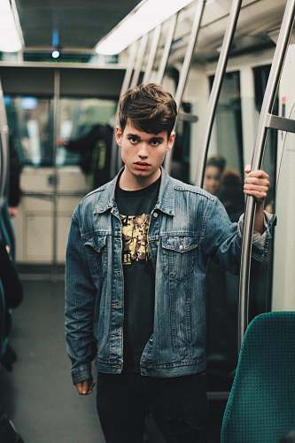people man wearing blue denim jacket standing inside train human