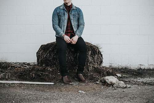 human man wearing blue denim western shirt sitting next to white concrete wall people