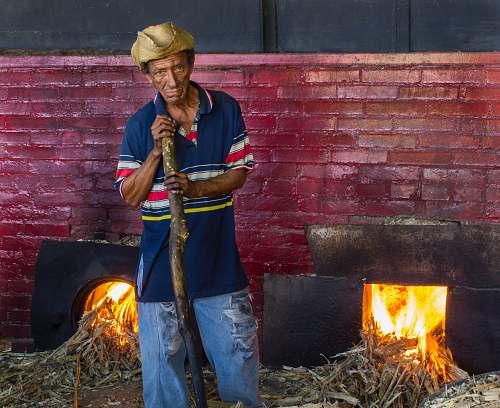 people man wearing blue polo shirt near firepit fire