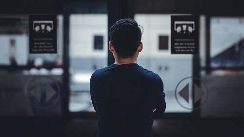 human man wearing blue top facing glass door people