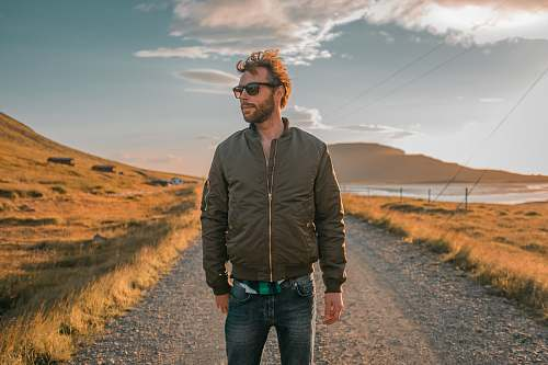 human man wearing bomber jacket standing in front of pathway people