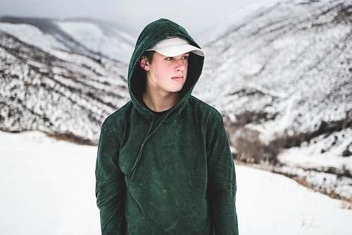 human man wearing green drawstring hoodie and white cap people