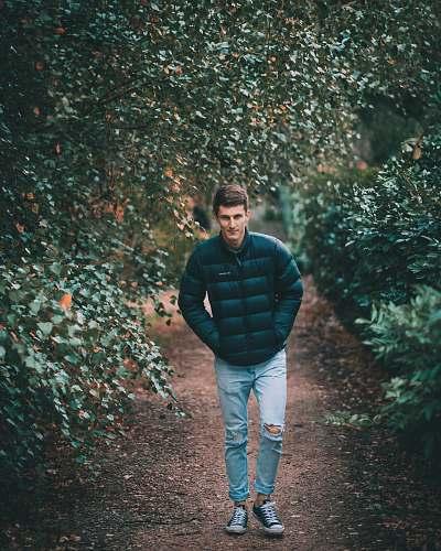 people man wearing puffer jacket between trees human