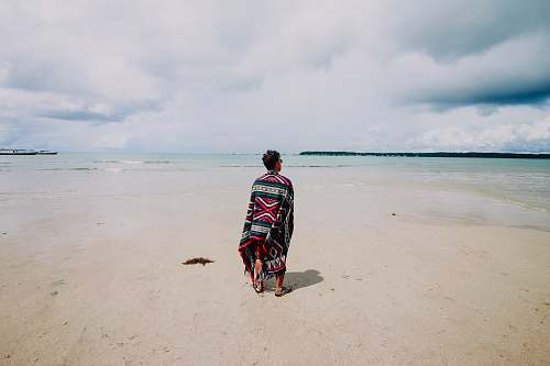 beach man wearing red and green scarf facing body of water ocean