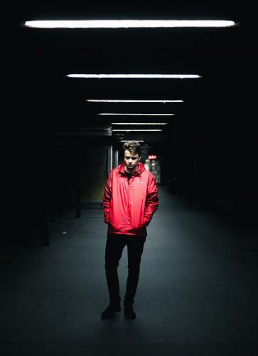 people man wearing red leather jacket standing inside dark area human