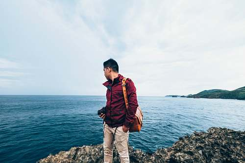 human man wearing red zip-up jacket standing on top of rocky cliff beside body of water during daytime people