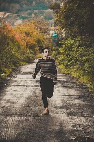 human man wearing sweater running on road between trees during daytime people