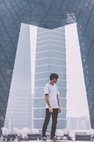 human man wearing white crew-neck shirt standing near the building people