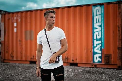 people man wearing white t-shirt near orange intermodal container human