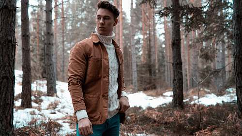 people man wearing white turtleneck sweater with brown jacket while standing in forest human