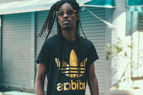 people man with dreadlocks hair wearing black and gold Adidas crew-neck shirt human
