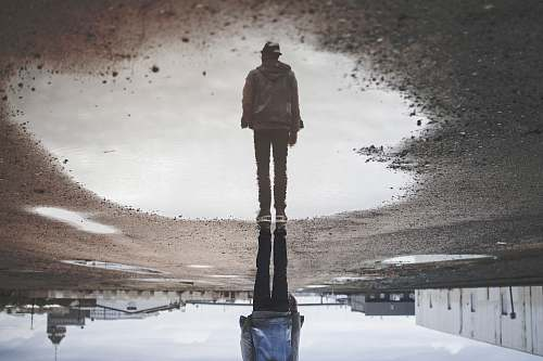 human man's reflection on body of water photography people