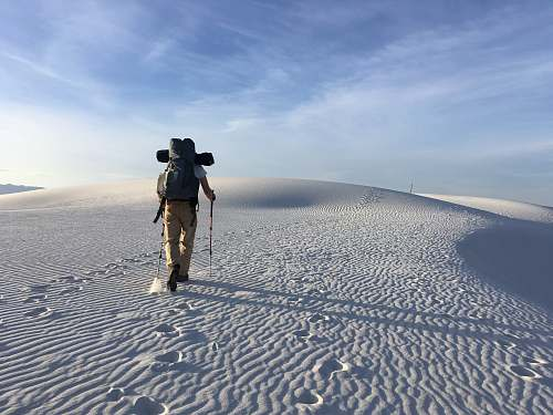 human person hiking on sand dunes under white skies during daytime people