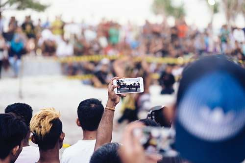 people person holding white smartphone while taking photo human