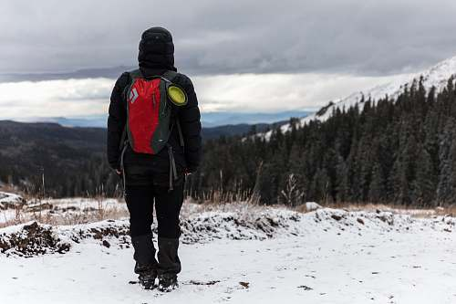 human person in black hoodie wearing red hydration pack and standing on top of hill covered of snow during cloudy sky people