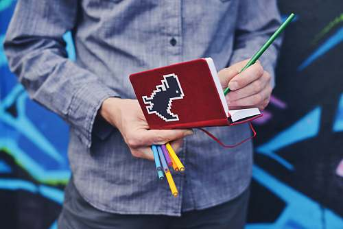 people person in blue dress shirt holding red book and colored pens human
