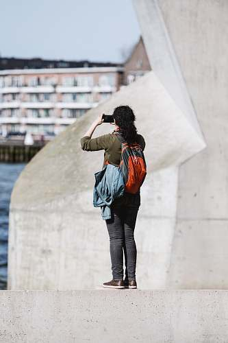 human person standing on concrete edge holding up smartphone taking photo people